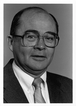 Black and white photo of Jim Laue where a suit and glasses.