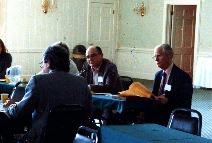 Old photo of people around a table during an academic conference. Identifiable are Jim Laue and John Burton.