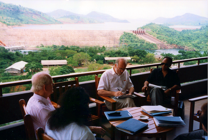 Shireen Kadivar, Amb. John McDonald, Chris Mitchell, and Wallace Warfield sit around a table with various folders and books on a balcony overlooking Akosombo Dam in Ghana.
