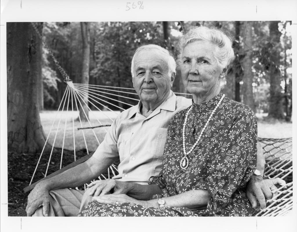 black and white photo of married couple on a hammock in a wooded area